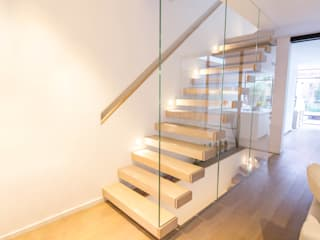 A minimalist floating staircase with oak-clad treads and glass wall balustrades.:  Corridor & hallway by Railing London Ltd