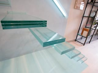 A single-flight cantilever staircase crafted in toughened, laminated glass by Railing London Ltd Сучасний