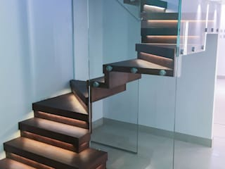 Elegant zig-zag staircase features walnut-clad treads and risers. Pasillos, vestíbulos y escaleras modernos de Railing London Ltd Moderno