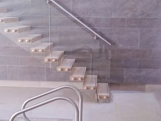 A custom-made floating staircase with oak-clad treads, a clear-glass balustrade and a wall-mounted stainless steel handrail. by Railing London Ltd Modern