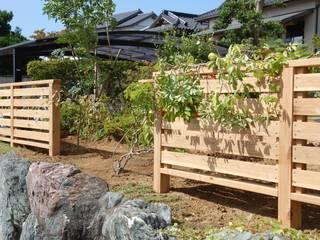 既存の植物を誘引したウッドフェンス: 実庭ガーデンデザインが手掛けた庭です。