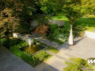 Eigentijdse tuin met zwembad en hoogteverschillen:  Tuin door Van Mierlo Tuinen   Exclusieve Tuinontwerpen