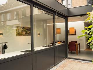 Luxe smalle aanbouw met keuken pal op het zuiden, aluminium schuifpui en lamellen zonwering:  Huizen door Joep van Os Architectenbureau, Modern