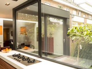 Luxe smalle aanbouw met keuken pal op het zuiden, aluminium schuifpui en lamellen zonwering: moderne Keuken door Joep van Os Architectenbureau