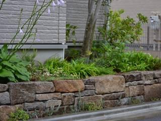 石積みのある庭: ツガワランドスケープが手掛けた庭です。