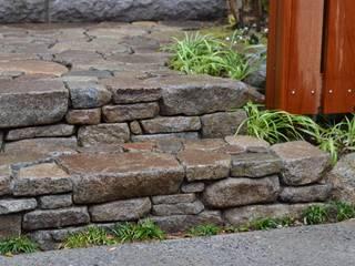 石積みのある庭: ツガワランドスケープが手掛けた廊下 & 玄関です。