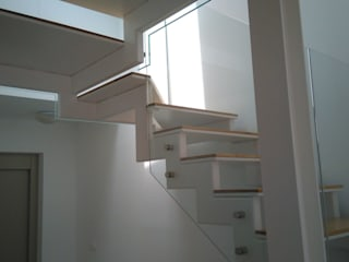 Detalle de la estructura metálica, pintada de blanco, y de la barandilla de vidrio totalmente transparente.: Pasillos y vestíbulos de estilo  de ALENTORN i ALENTORN ARQUITECTES, SLP