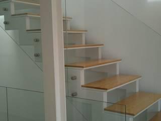 Detalle de la estructura metálica, pintada de blanco, de los escalones de madera y de la barandilla de vidrio totalmente transparente.: Pasillos y vestíbulos de estilo  de ALENTORN i ALENTORN ARQUITECTES, SLP