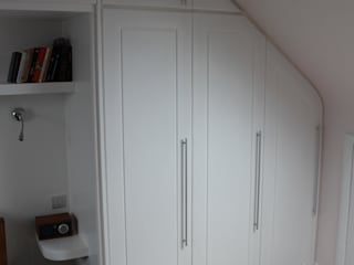 A wall of fitted wardrobes por TreeSaurus Clássico