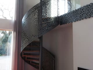 Laser cut screens - Spiral staircase and mezzanine apron.:  Corridor & hallway by miles and lincoln