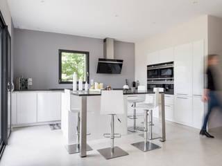 Cuisine SieMatic design en laque blanche avec un îlot central à Rennes: Cuisine de style  par IDKREA