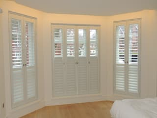 Full height bay windows with shutters:  Bedroom by Premier Blinds, Shutters & Awnings