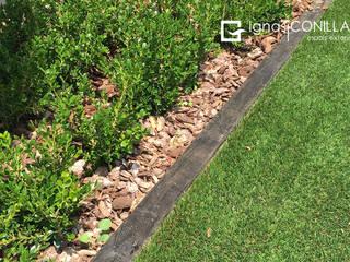 Jardín con césped artificial y vegetación: Jardines de estilo moderno de CONILLAS - exteriors