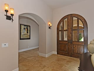 Arched double door entry:  Corridor & hallway by Metamorphysis Home Staging Services