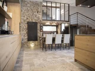 Salle à manger avec mur en pierre : Salle à manger de style de style Industriel par réHome