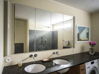 Wastafelblad van Spaanse hardsteen met twee wasplekken: modern Bathroom by B1 architectuur