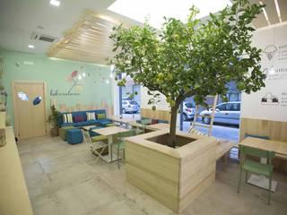 la zona relax di consumazione lenta con l'albero in primo piano: Gastronomia in stile  di Casaburi & Memoli Architetti