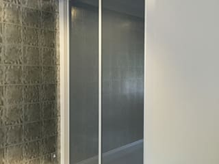 Tinted frosted glass sliding door wardrobe for cinema room.:   by Sliding Wardrobes World Ltd