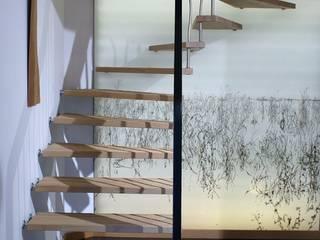 escalier suspendu senzu balustres courbes: Couloir et hall d'entrée de style  par ASCENSO