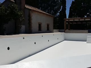 Piscina infinita sobre huerto de naranjos:  de estilo  de ARCOtectura