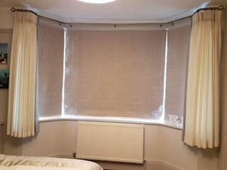 Leading edge pinch pleat voiles with blackout lined Roman blinds.:  Bedroom by Ashley Blinds & Curtains