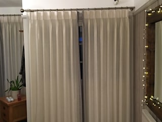 Leading edge pinch pleat voiles with blackout lined Roman blinds.:  Corridor & hallway by Ashley Blinds & Curtains