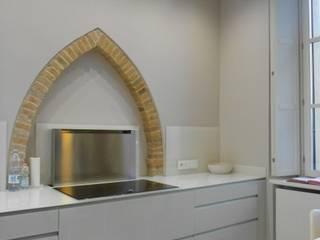 piano lavoro della cucina con la piastra ad induzione e cappa inserita nel piano ( a scomparsa) ed scorrevole in verticale Cucina moderna di Studio arch. Orban Agota Moderno
