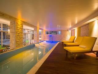 Detalle del deck del área de relax contiguo a la pileta. Se aprecia en el remate el totem con cascada.: Hoteles de estilo  por D&C Interiores
