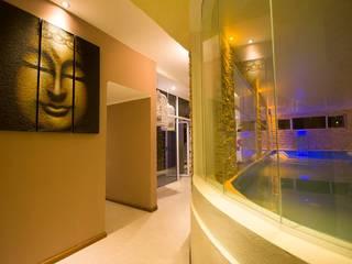 Vista del ingreso al spa. Se observa el muro curvo y vidriado del hidromasajes.: Hoteles de estilo  por D&C Interiores