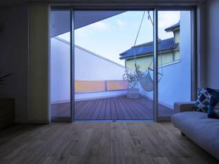 子世帯のテラスは親世帯の高天井に設けたハイサイドライトと緩やかに繋がる: 奥和田健建築設計事務所|okuwada architects officeが手掛けたベランダです。