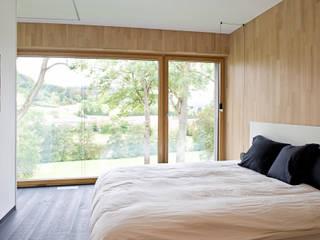 Maison passive hybride construite en béton et bois massif à Mersch (Luxembourg) Maisons Loginter Chambre moderne Bois