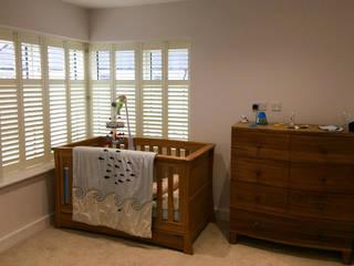 Full height shutters for sash windows:  Bedroom by Plantation Shutters Ltd