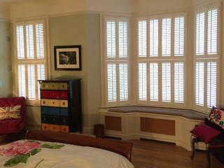 Tier on tier shutters for bay windows:  Bedroom by Plantation Shutters Ltd