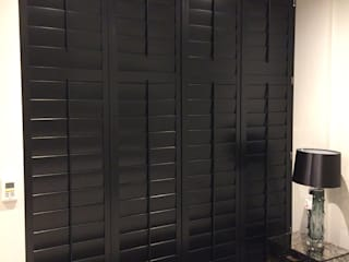 Wooden shutters for patio doors:  Bedroom by Plantation Shutters Ltd