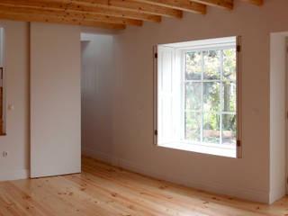Sala e passagem para a cozinha: Salas de estar  por Nuno Gouveia, arquiteto