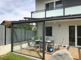 Terrassenverglasung in Anthrazit-Grau mit seitlichen Verglasungen zum schieben als Windschutz Schmidinger Wintergärten, Fenster & Verglasungen Moderner Wintergarten Aluminium/Zink Grau