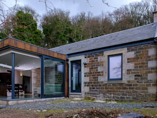 The rear extension to Woodend Cottage is clad in Corten steel and features large glass sliding doors:  Houses by Woodside Parker Kirk Architects