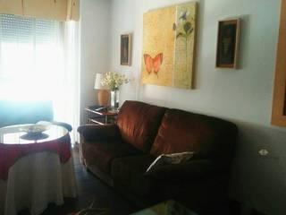 Una sala de estar con cierto exotismo:  de estilo  de CONSUELO TORRES