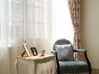 古典柔軟的傢俱搭配碎花窗簾迎著大面積的八角窗,營造輕鬆典雅的氛圍:  客廳 by 弘悅國際室內裝修有限公司