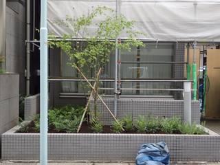 商業ビルリニューアルに伴う花壇の植栽植替え: DESIGNWORKSが手掛けた家です。
