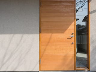 陽だまりの家: まる・ち設計が手掛けた玄関ドアです。