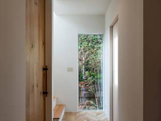 木と旅を愛する人の家: 東涌写真事務所が手掛けた廊下 & 玄関です。,