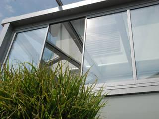 Wintergarten mit seitlich abgeschrägter Glasdachkonstrukion Schmidinger Wintergärten, Fenster & Verglasungen Moderner Wintergarten Glas Grau
