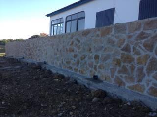 Execução e revestimento de muro com pedra rústica decorativa:   por Redializa - Construção e Reabilitação, Lda.