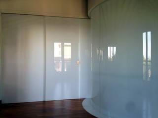 Attico A Roma con pareti vetrate curve e aperture irregolari: Pareti in stile  di Schiavello Architects Office