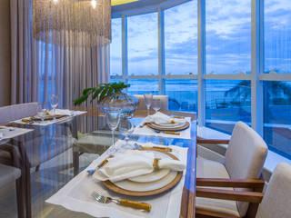 Projeto de interiores cria ambiente clean e contemporâneo na praia: Salas de jantar  por PROCAVE,Moderno