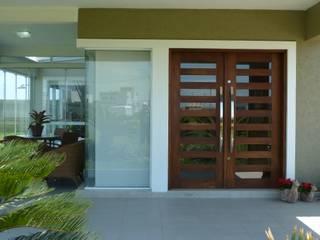 NA PRAIA, EM CONDOMÍNIO FECHADO: Portas de entrada  por Maciel e Maira Arquitetos,Moderno