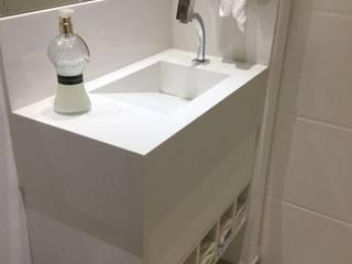Bancada esculpida branca para lavabo: Banheiros  por Estúdio Sá Arquitetura