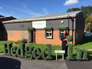 Hedged In logo in artificial hedge:   by Hedged In Ltd
