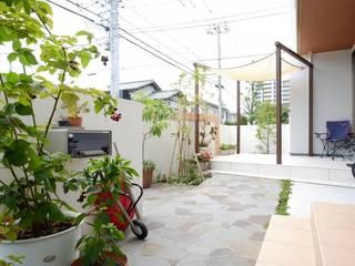 広い駐車場と家族がくつろげる白のタイルのテラス: 株式会社 風知蒼が手掛けた庭です。